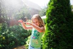Preschooler cute girl playing with garden sprinkler. Summer outdoor water fun in the backyard. stock image
