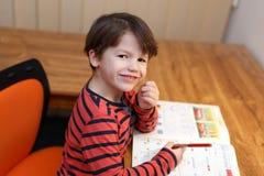 Preschooler genialna chłopiec rozwiązuje matematyki ćwiczenie Fotografia Stock