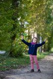 Preschooler girl in autumn park with maple leaves. Young toddler girl walking outdoor Royalty Free Stock Photography