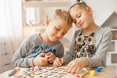 Preschoolers play and learn English letters using wooden alphabet. Preschooler girl and boy play and learn English letters using wooden alphabet royalty free stock photography