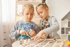 Preschoolers play and learn English letters using wooden alphabe. Preschooler girl and boy play and learn English letters using wooden alphabet stock photos
