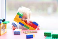 Preschooler girl building from plastic bricks. Happy child, cute blonde toddler girl building house from plastic blocks sitting next to a big window indoors at stock image