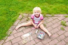 Preschooler girl drawing with chalk outdoors Royalty Free Stock Photos