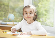 Preschooler girl drawing with pencils Royalty Free Stock Images