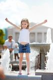 Preschooler girl playing with a city fountain Royalty Free Stock Images
