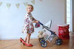 Preschooler girl playing with doll and pram Stock Photo