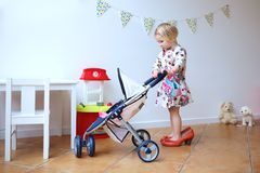 Preschooler girl playing with doll and pram Royalty Free Stock Photography