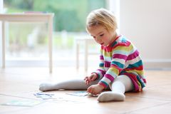 Preschooler girl playing with jigsaw puzzle Stock Photos
