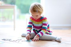 Preschooler girl playing with jigsaw puzzle Stock Photography