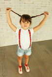 Preschooler girl. Playing with pigtails stock photos