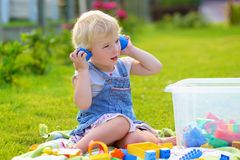 Preschooler girl playing with plastic blocks outdoors Royalty Free Stock Photography
