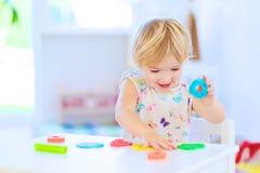 Preschooler girl playing with plasticine Stock Photos