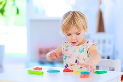 Preschooler girl playing with plasticine Stock Images