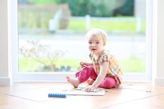 Preschooler girl playing with puzzles on the floor Royalty Free Stock Images
