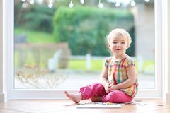 Preschooler girl playing with puzzles on the floor Stock Photos