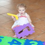 Preschooler girl playing with puzzles learning numbers Stock Photography