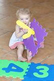Preschooler girl playing with puzzles learning numbers Stock Photos