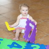 Preschooler girl playing with puzzles learning numbers Stock Photo
