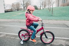 Preschooler girl riding pink bike bicycle in helmet on backyard road outside on spring autumn day stock photo