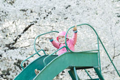 Preschooler girl wearing pink jacket and bucket hat sliding down old playground slide Royalty Free Stock Images