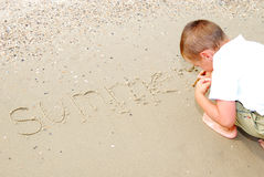 Preschooler human writing on sea sand Royalty Free Stock Photos