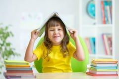 Preschooler  kid girl with book over her head Stock Photography