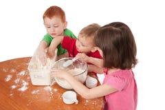 Preschooler kids making mess in kitchen. Three preschooler kids making a mess and cooking in kitchen Royalty Free Stock Images