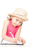Preschooler little girl wearing a hat at the table draws Royalty Free Stock Photo