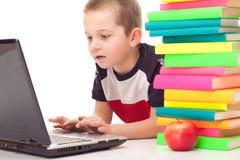 Preschooler no assoalho com livros e portátil imagens de stock royalty free