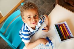 Preschooler Playing with a Box of Crayons. Charming Little Kid Looking Up and Playing with Crayons Royalty Free Stock Photography