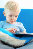 Preschooler playing games on a digital tablet Stock Photo