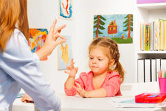 Preschooler playing hand game with teacher Stock Images