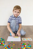 Preschooler playing mosaic. Preschooler playing in a mosaic in the room stock photos