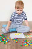 Preschooler playing mosaic. Preschooler playing in a mosaic in the room royalty free stock image
