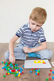 Preschooler playing mosaic. Preschooler playing in a mosaic in the room royalty free stock photography