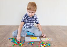 Preschooler playing mosaic. Preschooler playing in a mosaic in the room royalty free stock photos