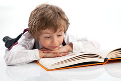 Preschooler reading book while lying on the floor Royalty Free Stock Photography