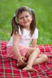 Preschooler sonriente de la muchacha que se sienta en la tela escocesa en parque Foto de archivo libre de regalías