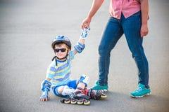 Preschooler spada podczas gdy rollerblading z matk? w parku fotografia stock