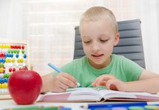 Preschooler, student doing homework at the desk at home Stock Photo
