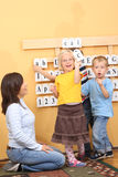 Preschoolers. Teacher and three preschoolers during lesson Stock Photos