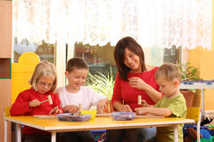 Preschoolers. Teacher and three preschoolers playing with wooden blocks Royalty Free Stock Photo