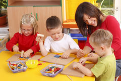 Preschoolers. Teacher and three preschoolers playing with wooden blocks Stock Photos