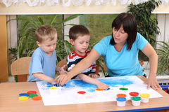Preschoolers and fingerpainting. Teacher two preschoolers and fingerpainting - education Stock Photos
