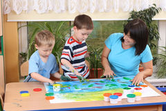 Preschoolers and fingerpainting. Teacher two preschoolers and fingerpainting - education Royalty Free Stock Image