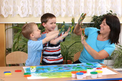 Preschoolers and fingerpainting. Teacher two preschoolers and fingerpainting - education Stock Image