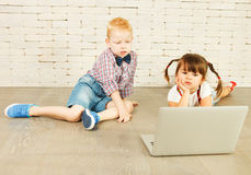 Preschoolers with laptop. On the floor Stock Photography