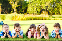 Preschoolers laughing. Five cute preschoolers laughing on the grass Royalty Free Stock Photos