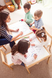Preschoolers learn letters. Overhead view of children in kindergarten learn letters and shapes coloring them Stock Photos