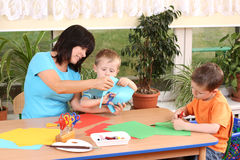 Preschoolers and manual skills. Teacher and two preschoolers making some decoration Royalty Free Stock Photos